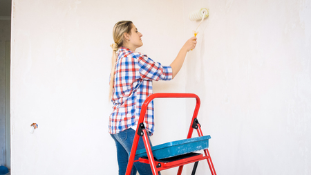 Portrait of beautiful young woman painting walls at her new home