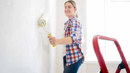 Portrait of smiling young girl painting walls with white paint