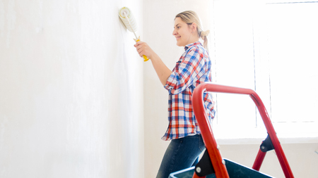 Happy smiling young woman doing renovation and painting walls with paint roller 写真素材
