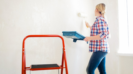 Young woman holding paint cuvette and painting walls with roller