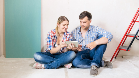 Happy young couple sitting on floor at house under construction and using digital tablet