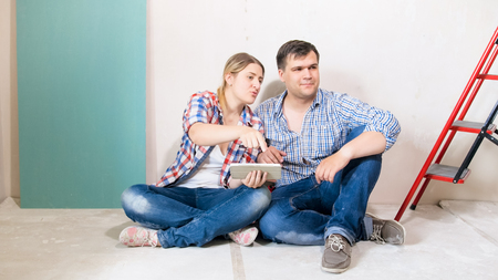 Happy young couple sitting on floor at their new house and choosing furniture from online shop