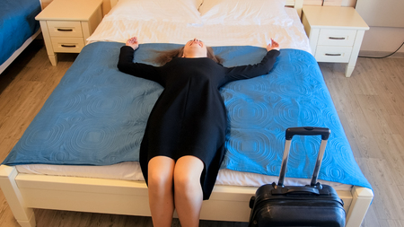 Young tired businesswoman resting on bed at hotel room after long flight