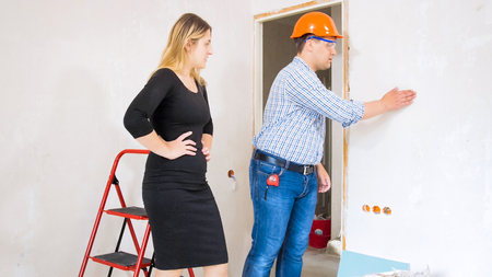 Construction worker showing new house to beautiful young businesswoman 写真素材