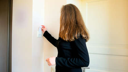 Young businesswoman inserting key card in electric swith at hotel room Stockfoto