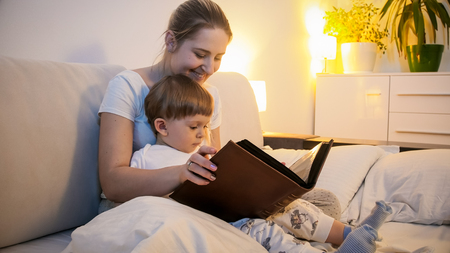 Toned portrait of smiling young woman reading story to her toddler son before going to sleep