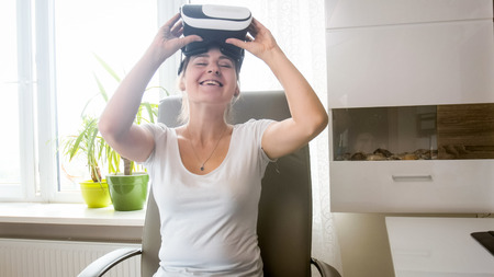 Portrait of smiling young woman taking off VR headset