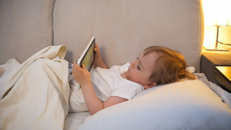 Cute toddler boy lying in bed and holding digital tablet