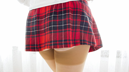 Closeup image of sexy woman showing bottom in extremely short skirt