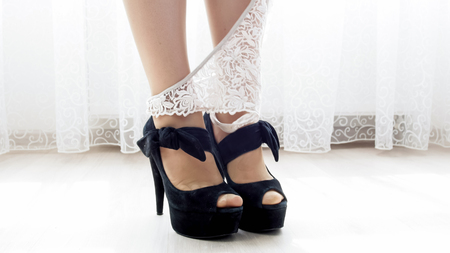 Closeup image of white lace panties on feet in high heels shoes