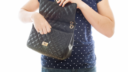 Closeup isolated image of young woman opens her black leather handbag Reklamní fotografie