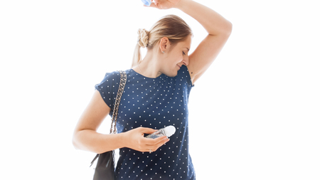 Isolated portrait of young woman smelling her armpits after applying deodorant Standard-Bild