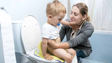 Young woman searing her toddler boy on toilet