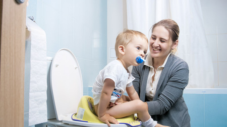 Portrait of smiling young mother teaching her toddler son using toilet Stock Photo