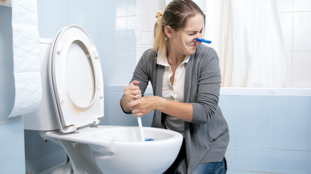 Portrait of young woman feeling disgust and bad smell cleaning toilet at home