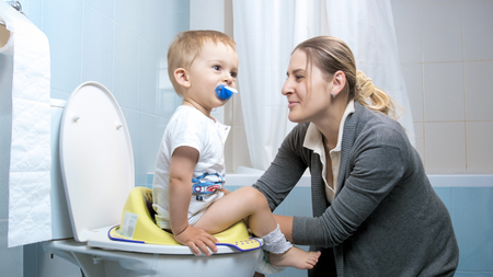 Young caring mother teaching her boy using toilet Standard-Bild