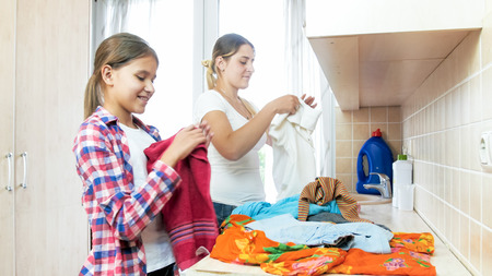 Portrait of smiling young mother with teenage daughter folding clothes after laundry Foto de archivo