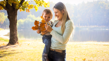 Portarit of laughing toddler boy looking at yellow autumn leaves with young mother