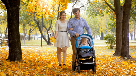 Happy smiling family walking with toddler son sitting in pram at autumn park