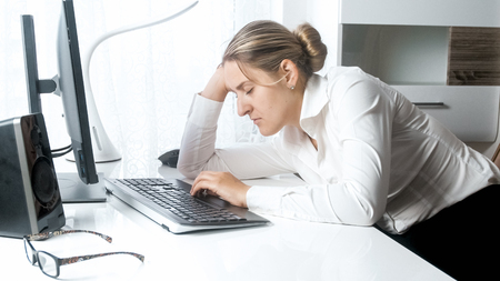 Portrait of tired female worker lening on hand while working on computer