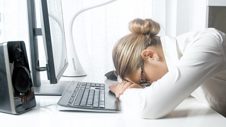 Closeup photo of young businesswoman sleeping on office desk Stock Photo