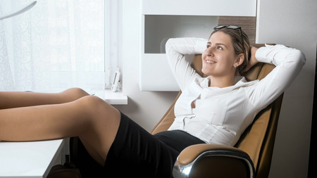 Portrait of beautiful smiling businesswoman putting feet in pantyhose on office desk