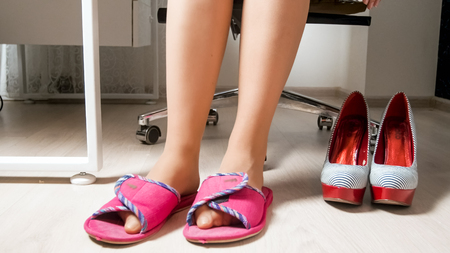 Young woman in office wearing comfortable slippers instead of high heels shoes