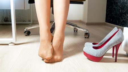 Closeup imagen de pies cansados en pantimedias después de un duro día de trabajo