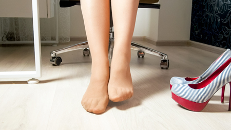 Closeup image of businesswoman resting feet under desk