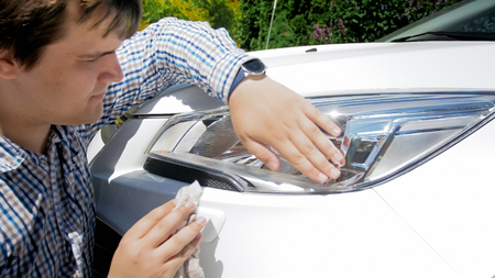 Portrait of young male driver cleaning car headlamps