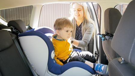 Beautiful smiling mother seating her toddler son in safety seat