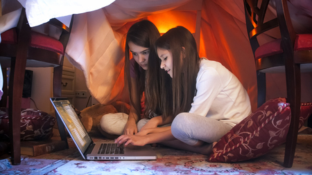 Two cute girls in pajamas sitting with laptop at tent made of blankets Stok Fotoğraf