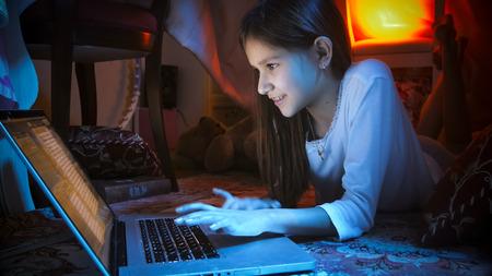Portrait of smiling girl in pajamas typing on laptop at night