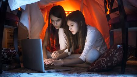 Two girls in pajamas using laptop at night Stock Photo