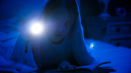 Portrait of girl lying in bed with flashlight at night
