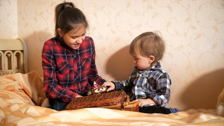 Cute toddler boy playing with elder sister on bed at bedroom Banque d'images