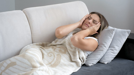 Portrait of young woman suffering from head ache lying on sofa Stock Photo
