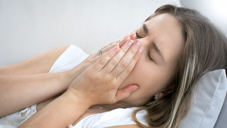Closeup portrait of young woman lying on sofa and coughing Stock Photo