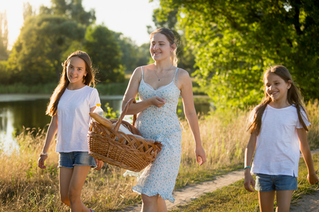 Portrait of beautiful young woman walking with two daughter near lake at sunset