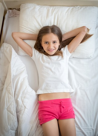 Portrait of beautiful smiling girl in pajamas lying on bed and looking up