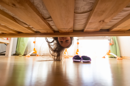 Portrait of teenage girl looking under the bed