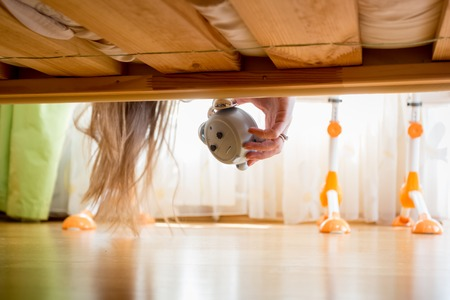 Closeup image of teenage girl taking ringing alarm clock from under the bed