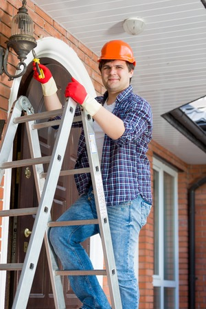 Portrait of smiling handyman climbing on stepladder to repair street lamps