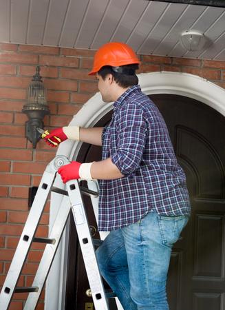 Male repairman standing on stepladder and repairing outdoor lamp Zdjęcie Seryjne