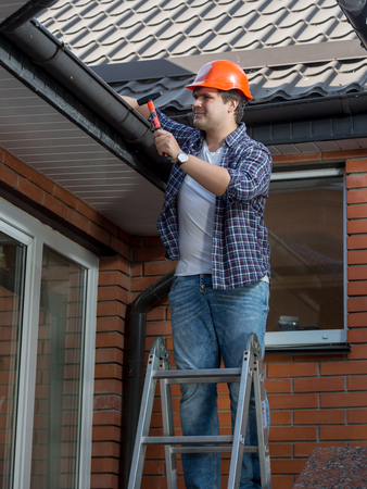 Portrait of smiling male carpenter making building house rooftop