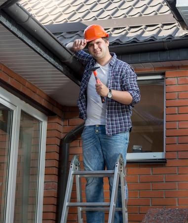 Portrait of smiling carpenter in hardhat standing on top of stepladder