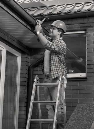 Black and white portrait of male carpenter repairing house roof
