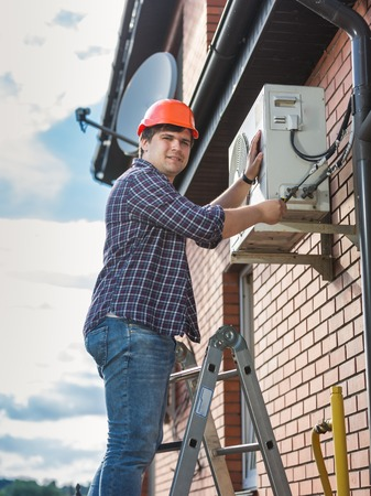 Smiling male technician repairing outdoor air conditioner unit Stock Photo