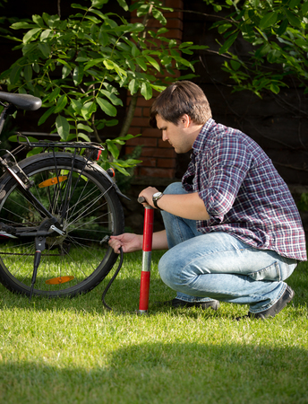 Young man pumping bicycle wheel with air pump