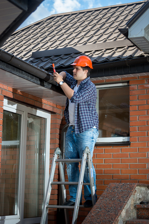 Young male builder standing on stepladder and repairing rooftop